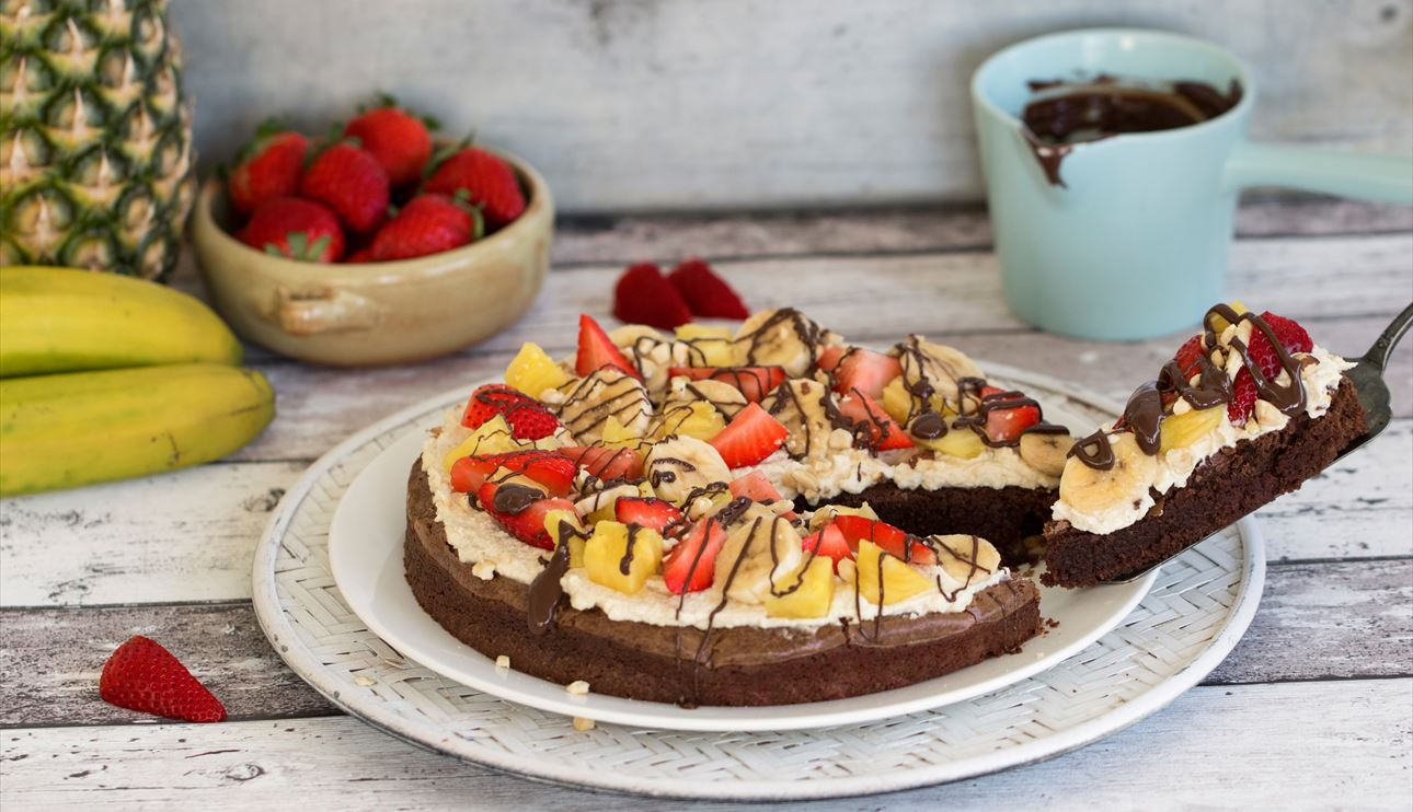 Brownie pizza con nata y frutas